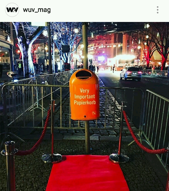 Streetphoto of a bin which has written Very Important Papierkorb written on it with a red carpet in front of it