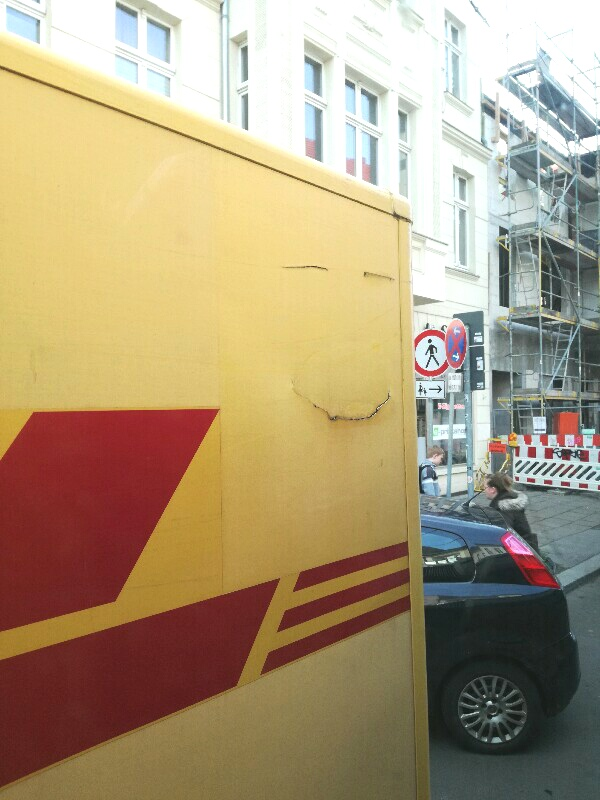 Holes on a DHL truck that look like a smiling face. A photo by Stefan Klenke