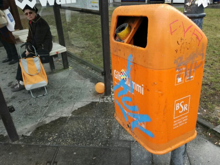 Three random orange objects at a bus stop - streetphoto by Stefan Klenke